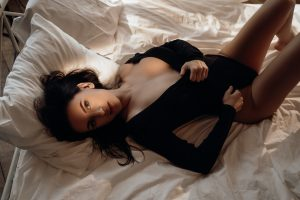 Goregeous woman showing her body wearing body costume among bed sheets